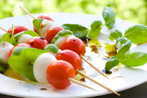 Plate of tomatoes, mozzarella balls, and basil on skewers in outdoor setting